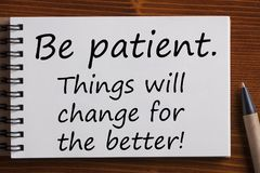 Be patient written on notebook. Notebook with text ` Be patient.Things will change for the better!`on wooden background Stock Photo