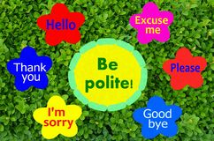 Be polite message on flowers fixed on green background Royalty Free Stock Photo