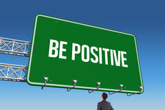 Be positive against blue sky. The word be positive and businessman standing with hands on hips against blue sky Stock Images