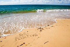 Be positive. Creative motivation concept. Be positive. Creative motivation concept written in the sand at the beach Royalty Free Stock Photography