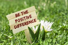 Be the positive difference. On wooden sign in garden with spring flower Royalty Free Stock Photography