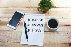 Be Positive Improve Inspire, Motivational Words Quotes Concept. Be positive improve inspire words letter, written on notepad, work desk top view. Motivational royalty free stock photography