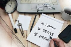 Be Positive Improve Inspire, Motivational Words Quotes Concept. Be positive improve inspire words letter, written on notepad, work desk top view. Motivational stock photos