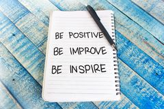 Be Positive Improve Inspire, Motivational Words Quotes Concept. Be positive improve inspire words letter, written on notepad, work desk top view. Motivational royalty free stock image
