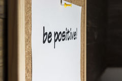 Be positive!. Be positive pinned on cork board Royalty Free Stock Photography