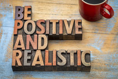 Be positive and realistic. Motivational text in vintage letterpress wood type printing blocks stock image