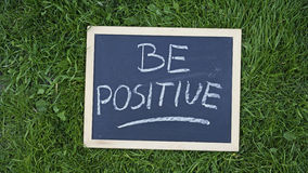 Be positive written. On a chalkboard in the nature Stock Photos