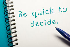 Be quick to decide - Office table top view. Notepad with text and pen Stock Images