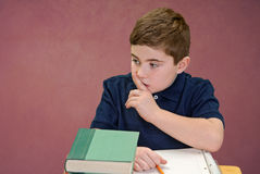 Be Quiet. Boy at school with finger to lips to quiet someone stock photo