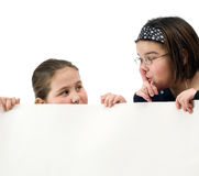 Be Quiet. Two young girl trying to spy over a white wall, isolated against a white background Stock Photos