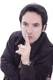 Be quiet. Young man with his finger on his lips Stock Photos