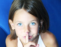 Be quiet gesture. A caucasian child with her forefinger to her mouth saying shhh to be quiet Stock Image
