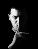 Be quiet. Man showing be quiet sign, low key and black and white techniques Stock Photos
