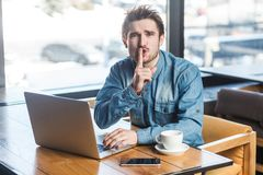 Be quiet please! Portrait of handsome severe bearded young freelancer in blue jeans shirt are sitting in cafe and working on. Laptop, lean finger on mouth stock image