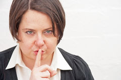 Be quiet please. Young woman teacher asking class to be quiet with finger to her lips Royalty Free Stock Image