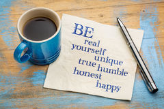 Be real, yourself, unique, true, humble, honest and happy. Inspirational handwriting on a napkin with a cup of espresso coffee royalty free stock photography