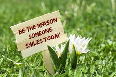 Be the reason someone smiles today. On wooden sign in garden with white spring flower Stock Images