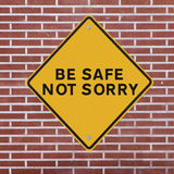 Be Safe Not Sorry. Workplace safety reminder on a red brick wall background Royalty Free Stock Image