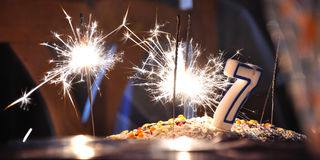 Be seven. Sparkler lightning with unlit candle shaped number seven on a cake for a birthday of a child Royalty Free Stock Photo