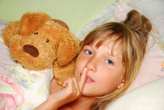 Be silent ! I am sleepy... Sleepy  young girl lying in bed with mascot asking to be silent Stock Photos