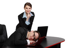 Be Silent !. The secretary keeps silence while her tired boss dozing on the desk in front of his notebook Stock Image