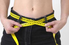 Be slimming. Young woman with tape measure Stock Images