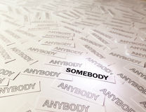 Be Somebody. A lot of anybody and accented somebody, words written on white papers Stock Photography