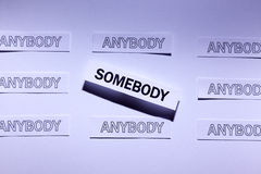 Be Somebody. A lot of anybody and accented somebody, words written on white papers Royalty Free Stock Photos