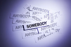 Be Somebody. A lot of anybody and accented somebody, words written on white papers Stock Images
