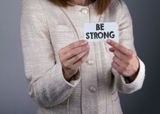 Be strong. Businesswoman holding a card with a message text.  Stock Photography