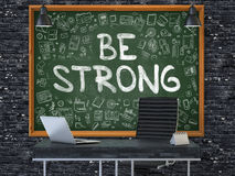 Be Strong on Chalkboard in the Office. 3D. Green Chalkboard with the Text Be Strong Hangs on the Dark Brick Wall in the Interior of a Modern Office Royalty Free Stock Photo