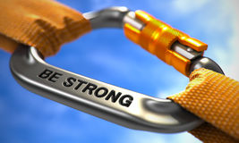 Be Strong on Chrome Carabine with a Orange Ropes. Be Strong. Motivational Quote on Chrome Carabine with a Orange Ropes. Selective Focus Royalty Free Stock Photography