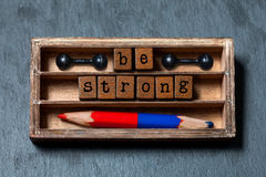 Be strong conceptual image. Vintage blocks with text in wooden box, blue red pencil and dumbbells. Gray stone background. Macro Stock Images