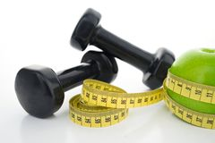 Be strong!. Isolation image of dumbbells and measure tape on a white background Royalty Free Stock Photo