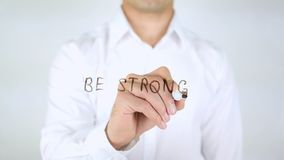Be Strong, Man Writing on Glass, Handwritten. High quality Stock Photo