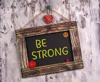 Be strong written on Vintage sign board stock image