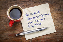 Be strong. You never know who you are inspiring. Inspirational handwriting on a napkin with a cup of coffee Stock Photo