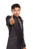Be successful. Young businessman in dark grey coat and steel-blue shirt standing isolated on white background with thumbs up Stock Images