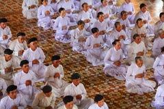 Be tid, män och kvinnor som tillber på Cao Dai Royaltyfria Bilder