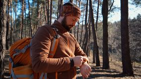 Be on time in travel and adventures. Waist up portrait of bearded man traveler, with backpack, uses technology sports watch for stock photo