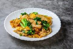 Be*wegen-gebraden Verse rijst-Bloem Noedels met Gesneden Varkensvlees, Ei en Boerenkool stock foto