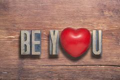 Be you heart wooden. Be you phrase combined on vintage varnished wooden surface with heart symbol inside royalty free stock photos