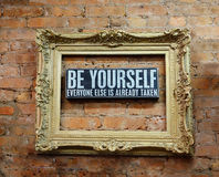 BE YOURSELF. Antique gold frame into which is inserted a plate with the inscription: BE YOURSELF EVERYONE IS ALREADY TAKEN royalty free stock photos