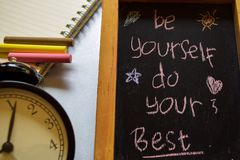 Be yourself do your best on phrase colorful handwritten on chalkboard, alarm clock with motivation and education concepts. stock image