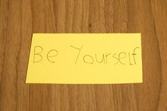 Be yourself handwrite on a yellow paper with a pen on a table. Composition stock photos