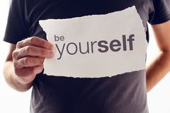 Be Yourself motivational message. Man holding paper with Be Yourself motivational message Stock Image