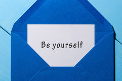 Be yourself - wish at blue envelope on rustic table Stock Image