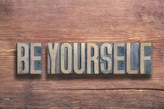 Be yourself wood. Be yourself phrase combined on vintage varnished wooden surface stock image