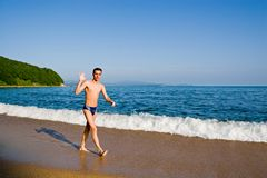 Beach. The young man goes on a beach, welcomes a hand.Evening Stock Photos