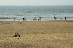 At the beach. People sitting and swimming at the beach Royalty Free Stock Photography